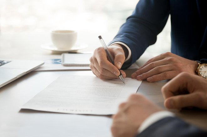 Close up image of businessman hand putting personal signature on contract document in presence of business partner. Starting successful partnership with entrepreneur or companie, making good deal